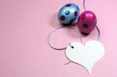 Os ovos da páscoa cor-de-rosa e azuis do às bolinhas com o presente branco do coração etiquetam - horizontal com espaço da cópia. Fotografia de Stock Royalty Free