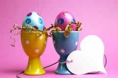 Os ovos da páscoa cor-de-rosa e azuis em uns copos de ovo do às bolinhas com o presente branco do coração etiquetam Imagem de Stock