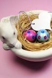Os ovos da páscoa cor-de-rosa e azuis no coelho branco rolam - vertical. Imagem de Stock
