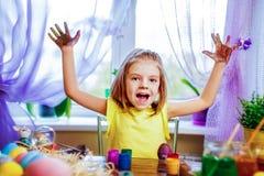 Os ovos da páscoa de pintura da menina feliz, criança pequena têm em casa o divertimento Feriado da mola foto de stock