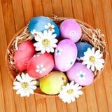 Os ovos da páscoa decorados com margaridas dobraram dentro uma cesta Fotografia de Stock Royalty Free