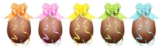 Os ovos da páscoa do chocolate com fita curvam-se no backgrou branco Imagens de Stock