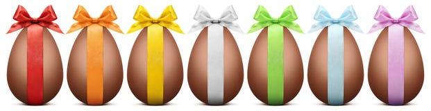 Os ovos da páscoa do chocolate com fita curvam-se no backgrou branco Imagens de Stock Royalty Free