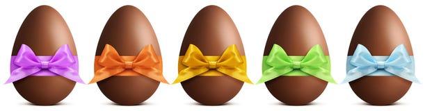 Os ovos da páscoa do chocolate com fita curvam-se no fundo branco Imagens de Stock Royalty Free