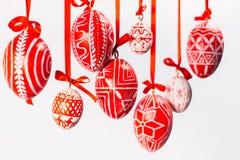 Os ovos da páscoa do close up com teste padrão ucraniano popular penduram em fitas vermelhas com curvas no fundo branco Ovos trad Foto de Stock