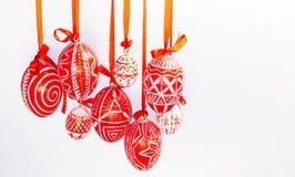 Os ovos da páscoa do close up com teste padrão ucraniano popular penduram em fitas vermelhas do lado esquerdo no fundo branco Ovo Fotografia de Stock Royalty Free