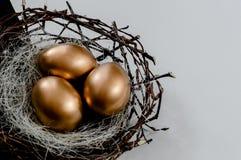 Os ovos da páscoa dourados nos pássaros aninham-se sobre o fundo rústico Copyspace do fundo do sumário do conceito do feriado da  fotografia de stock royalty free