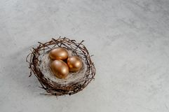 Os ovos da páscoa dourados nos pássaros aninham-se sobre o fundo rústico Copyspace do fundo do sumário do conceito do feriado da  foto de stock royalty free