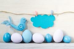 Os ovos da páscoa e o pássaro nas cores pastel com um cartão vazio nublam-se em um fundo de madeira claro Imagem de Stock Royalty Free