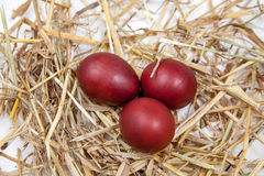 Os ovos da páscoa em uma palha aninham-se no fundo de madeira rústico E feliz Fotos de Stock Royalty Free