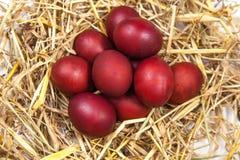 Os ovos da páscoa em uma palha aninham-se no fundo de madeira rústico E feliz Imagens de Stock
