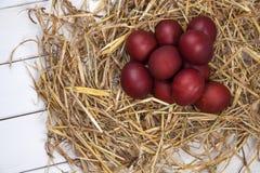Os ovos da páscoa em uma palha aninham-se no fundo de madeira rústico E feliz Imagem de Stock