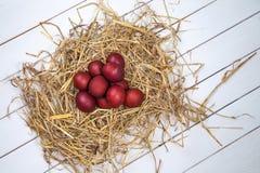 Os ovos da páscoa em uma palha aninham-se no fundo de madeira rústico E feliz Foto de Stock