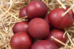 Os ovos da páscoa em uma palha aninham-se no fundo de madeira rústico E feliz Fotografia de Stock