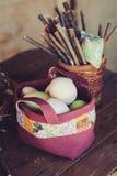 Os ovos da páscoa na edredão feito a mão ensacam na tabela de madeira com decorações Foto de Stock
