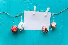Os ovos da páscoa pasteis coloridos na bacia com papel vazio etiquetam para o tex Fotos de Stock