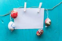 Os ovos da páscoa pasteis coloridos na bacia com papel vazio etiquetam para o tex Fotos de Stock Royalty Free