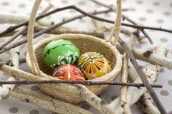 Os ovos da páscoa pintados coloridos na cesta de vime marrom em ramos, vida tradicional da Páscoa ainda, pássaros de madeira anin Imagem de Stock