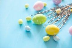 Os ovos da páscoa pintados em cores diferentes aproximam os galhos do salgueiro Imagem de Stock