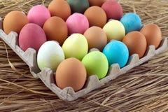 Os ovos da páscoa pintados encontram-se nas fileiras dentro das pilhas em uma palha Imagem de Stock