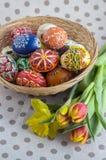 Os ovos da páscoa pintados feitos a mão caseiros na cesta de vime, tradicional handcraft ovos Imagem de Stock