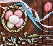 Os ovos da páscoa, ramos do bichano, coloriram fitas, fundo de madeira, Fotos de Stock Royalty Free