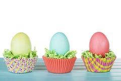 Os ovos da páscoa tingidos em um ninho de confetes e de copo da grama verde endurecem Imagem de Stock Royalty Free