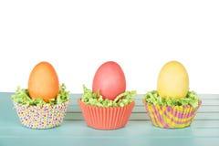 Os ovos da páscoa tingidos em um ninho de confetes e de copo da grama verde endurecem Imagens de Stock Royalty Free