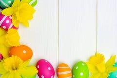 Os ovos da páscoa e os narcisos amarelos encurralam a beira sobre a madeira branca Imagem de Stock Royalty Free