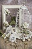 Os ovos da páscoa em uma gaiola, saltam as flores brancas, ovos de codorniz, coelhos brancos Fotografia de Stock