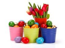 Ovos da páscoa em umas cubetas coloridas da lata Fotos de Stock Royalty Free