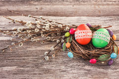 Os ovos da páscoa no ninho e no salgueiro pequenos ramificam no fundo de madeira Fotografia de Stock