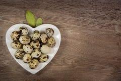 Os ovos de codorniz em um coração deram fôrma à placa na madeira Imagem de Stock Royalty Free