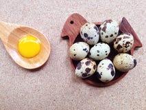 Os ovos de codorniz no pássaro de madeira deram forma a pires e a gema em s de madeira Imagem de Stock Royalty Free