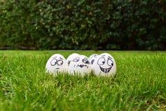 Os ovos do caráter huddled junto com a expressão facial engraçada na grama foto de stock royalty free