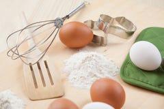 Os ovos, farinha, molde do biscoito e whisk na placa de madeira foto de stock royalty free