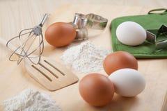 Os ovos, farinha, molde do biscoito e whisk na placa de madeira imagens de stock