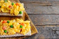 Os ovos mexidos deliciosos com ervilhas e cenouras na omeleta friável dos ovos mexidos do brinde brindam a receita Fundo de madei imagem de stock