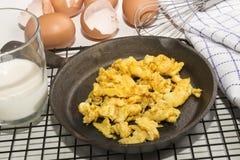 Os ovos mexidos orgânicos em um ferro fundido filtram e batem Imagem de Stock Royalty Free