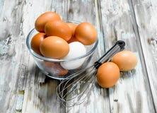 Os ovos na bacia com whisk foto de stock royalty free
