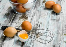 Os ovos na bacia com whisk imagem de stock