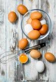 Os ovos na bacia com whisk fotos de stock