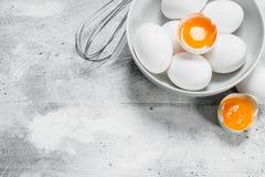 Os ovos na bacia com whisk imagem de stock royalty free