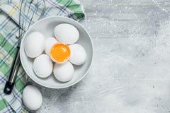 Os ovos na bacia com whisk fotografia de stock