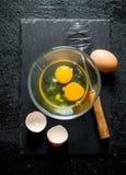 Os ovos na bacia com whisk foto de stock