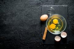 Os ovos na bacia com whisk fotos de stock royalty free