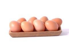 os ovos na bacia quadrada de madeira isolaram o fundo branco Foto de Stock