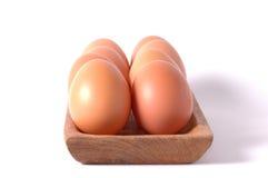 os ovos na bacia quadrada de madeira isolaram o fundo branco Foto de Stock Royalty Free