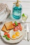 Os ovos, o brinde e o bacon por um verão tomam o café da manhã Fotos de Stock