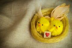 Os pássaros acoplam-se no ninho dourado com o filhote decorado do açúcar mascavado imagem de stock